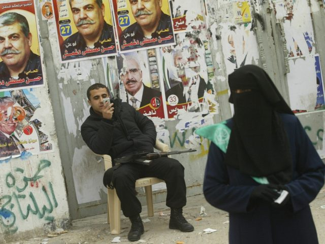 GAZA CITY, -: A Palestinian policeman plays with his mobile phone as a militant from the Islamic Resistance Movement Hamas distributes flyers outside a polling station in Gaza City 25 January 2006. Palestinians voted in their first general election for a decade, with the Islamists of Hamas presenting the Fatah …