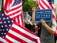 "Protesters standing amid US flags hold up placards that read ""President Trump, please liberate Hong Kong"" as they gather at Victoria Park to participate in an anti-government march in Hong Kong on July 21, 2019. - Hong Kong is bracing for another huge anti-government march on July 21 afternoon with …"