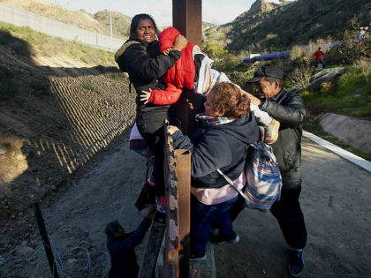 TIJUANA, MEXICO - JANUARY 06: Honduran migrants climb over the U.S.-Mexico border fence along on January 6, 2019 in Tijuana, Mexico. The U.S government is going into the third week of a partial shutdown with Republicans and Democrats at odds on agreeing with President Donald Trump's demands for more money …