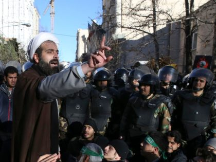 urrounded by policemen, a Muslim cleric addresses a crowd during a demonstration to denounce the execution of Saudi Shiite Sheikh Nimr al-Nimr, seen in poster, in front of the Saudi embassy in Tehran, Iran, Sunday, Jan. 3, 2016. Saudi Arabia announced the execution of al-Nimr on Saturday along with 46 …