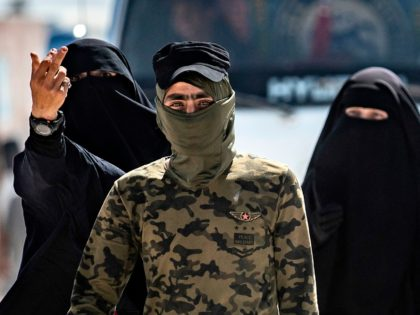 An internal security patrol member escorts women, reportedly wives of Islamic State (IS) group fighters, in the al-Hol camp in al-Hasakeh governorate in northeastern Syria, on July 23, 2019. - Stabbing guards, stoning aid workers and flying the Islamic State group's black flag in plain sight: the wives and children …