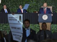 A protester holds a sign as US President Donald Trump speaks during an event commemorating the 400th Anniversary of the First Representative Legislative Assembly in Jamestown, Virginia on July 30, 2019. - President Donald Trump on Tuesday visited the site of the first permanent English settlement in the United States …