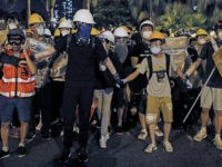 In this Sunday, July 14, 2019, photo, protesters wearing protection gears as they prepare to face-off with policemen on a street in Sha Tin District in Hong Kong. What began as a protest against an extradition bill has ballooned into a fundamental challenge to the way Hong Kong is governed …