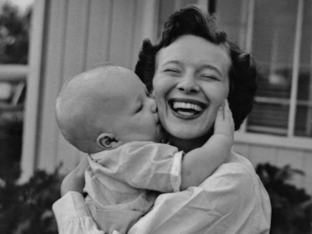A woman laughs as a baby hugs and kisses her, circa 1945. (Photo by Pictorial Parade/Archive Photos/Getty Images)