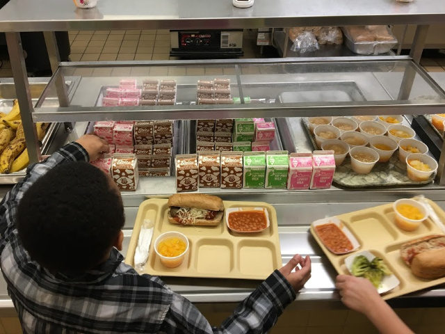 FILE - In this Jan. 25, 2017, file photo, students fill their lunch trays at J.F.K Elementary School in Kingston, N.Y., where all meals are now free under the federal Community Eligibility Provision. A donor inspired by a tweet raised money to pay off lunch debt in districts around the …