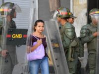 A woman walks by as members of Venezuela's Bolivarian National Guard block stand guard in the surroundings of the Federal Legislative Palace, which houses both the opposition-led National Assembly and the pro-government National Constituent Assembly, in Caracas on May 15, 2019. - Opposition leader Juan Guaido accused the Venezuelan government …