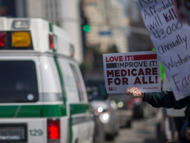 An ambulance passes people protesting Trump administration policies that threaten the Affordable Care Act, Medicare and Medicaid, near the Wilshire Federal Building on January 25, 2017 in Los Angeles, California. / AFP / DAVID MCNEW (Photo credit should read DAVID MCNEW/AFP/Getty Images)