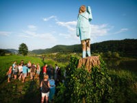 People gather around what conceptual artist Ales 'Maxi' Zupevc claims is the first ever monument of Melania Trump, set in the fields near the town of Sevnica, US First Ladys hometown, during a small inauguration celebration on July 5, 2019. (JURE MAKOVEC/AFP/Getty Images)