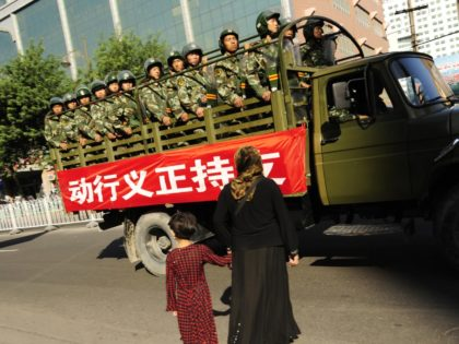 A Muslim ethnic Uighur woman and her daughter try to cross the road as Chinese paramilitary police drive past near the closed Grand Bazaar in the ethnic Uighur area of Urumqi, in China's farwest Xinjiang region, on July 9, 2009. Riot police and soldiers kept a strong presence in China's …