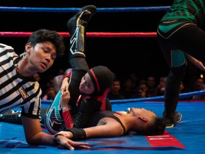 "This picture taken on July 6, 2019 shows the hijab-wearing Malaysian wrestler known as Nor ""Phoenix"" Diana (C) wrestling with a male opponent during a match organised by Malaysia Pro Wrestling in Kuala Lumpur. - A hijab-wearing, diminutive Malaysian wrestler known as ""Phoenix"" cuts an unusual figure in the ring, …"
