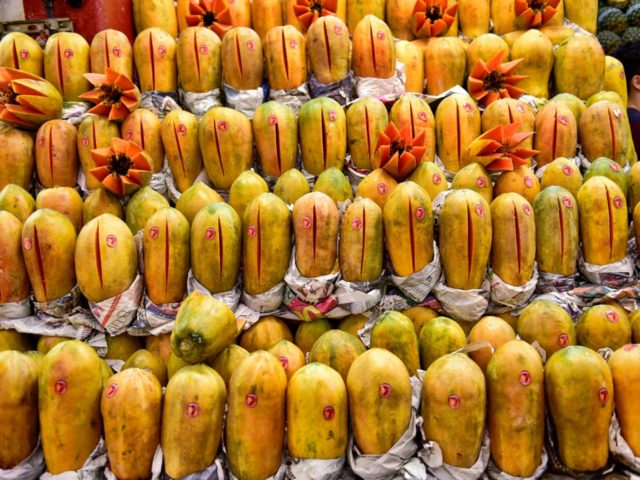 """A man sells papayas at the """"Central de Abasto"""" wholesale market in Mexico City on December 21, 2017. Some 500,000 people and 62,000 vehicles a day visit the Central de Abasto market on the east side of Mexico City to buy and sell avocados, tomatoes and about 15,000 other products. …"""