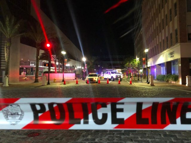 TOPSHOT - This photo shows a police car behind police tape blocking a street leading to the Jacksonville Landing area in downtown Jacksonville, Florida, August 26, 2018, where three people were killed, including the gunman, and 11 others wounded. - Two people were killed and 11 others wounded on August …