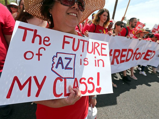 PHOENIX, AZ - APRIL 26: Arizona teachers march toward the State Capitol as part of a rally for the #REDforED movement on April 26, 2018 in Phoenix, Arizona. Teachers state-wide staged a walkout strike on Thursday in support of better wages and state funding for public schools. (Photo by Ralph …