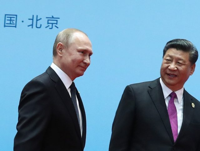 TOPSHOT - China's President Xi Jinping (R) and Russia's President Vladimir Putin smile during the welcoming ceremony on the final day of the Belt and Road Forum in Beijing on April 27, 2019. - Chinese President Xi Jinping urged dozens of world leaders on April 27 to reject protectionism and …