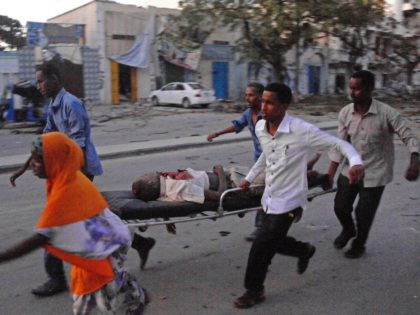 People carry a victim of a terror attack at the Ambassador Hotel, after Somalia's Al-Qaeda-linked Shabaab on June 1, 2016, launched a deadly attack on a top Mogadishu hotel popular with MPs, setting off a car bomb and fighting security forces inside the complex. Somalia's Al-Qaeda-linked al-Shabaab group was chased …