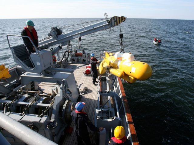 Navy members pull up a submersible device during the Operation Open Spirit, the latest in a long drive to clear the potentially deably devices from the baltic, on the deck of a Lithuanian mine-sweeper, off the coast of Klaipeda, in the Baltic Sea, on September 7, 2010. Ships from seven …