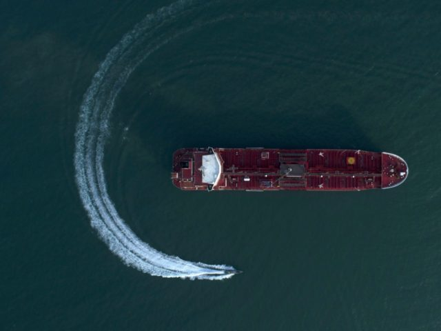 In this Sunday, July 21, 2019 photo, an aerial view shows a speedboat of Iran's Revolutionary Guard moving around the British-flagged oil tanker Stena Impero which was seized in the Strait of Hormuz on Friday by the Guard, in the Iranian port of Bandar Abbas. Global stock markets were subdued …