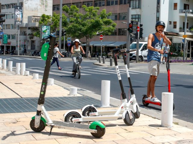 A man rides an electric scooter in the streets of the Israeli coastal town of Tel Aviv on May 30, 2019. - Israelis in the countrys economic capital Tel Aviv have embraced electric scooters and their smart-phone rental systems, using them to zip along Mediterranean beaches and avoid heavy traffic …