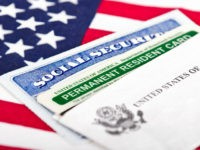 Social Security card and permanent resident on USA flag - stock photo United States of America social security and green card with US flag on the background.
