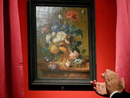 """The """"Vase of Flowers"""" painting by Jan van Huysum, is unveiled during a ceremony at the Pitti Palace, part of the Uffizi Galleries, in Florence, Italy, Friday, July 19, 2019. Germany returned the Dutch still-life after it was stolen by Nazi troops during WWII. (AP Photo/Gregorio Borgia)"""