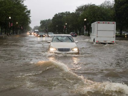 Heavy rainfall flooded the intersection of 15th Street and Constitution Ave., NW, stalling cars in the street, Monday, July 8, 2019, in Washington. (AP Photo/Alex Brandon)