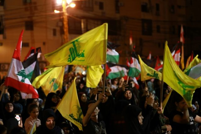 Lebanese supporters of the Shiite Hezbollah party wave Lebanese national and party (yellow) flags, as they march in Beirut in May
