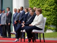 Merkel sits during anthems after shaking spells