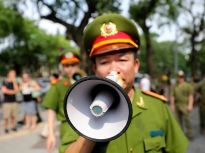 A Vietnamese police officer uses a speaker to order pedestrians including journalists to leave a closed area near the Chinese Embassy in Hanoi, Vietnam on Sunday, May 18, 2014. Vietnamese authorities forcibly broke up small protests against China in two cities on Sunday, after deadly anti-China rampages over a simmering …
