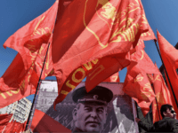 TOPSHOT - A Russian Communist party activist holds a red flag as he stands next to a banner with a portrait of late Soviet leader Joseph Stalin during a May Day rally in central Moscow on May 1, 2016. / AFP / KIRILL KUDRYAVTSEV (Photo credit should read KIRILL KUDRYAVTSEV/AFP/Getty …
