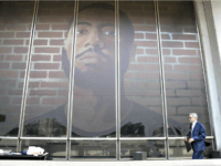 Philadelphia DA Larry Krasner walks by a self-portrait made by a formerly incarcerated artist in Philadelphia, Pennsylvania, on October 3, 2018. The mural is part of a large-scale art project focusing on solutions for mass incarceration. Matt Rourke/AP