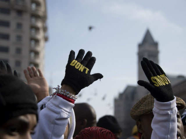 "Lesley McSpadden (C), mother of Ferguson shooting victim Michael Brown, holds up her hands with gloves that say ""Don't Shoot"" during the ""Justice For All"" march in Washington, DC, December 13, 2014. Thousands of people descended on Washington to demand justice Saturday for black men who have died at the …"