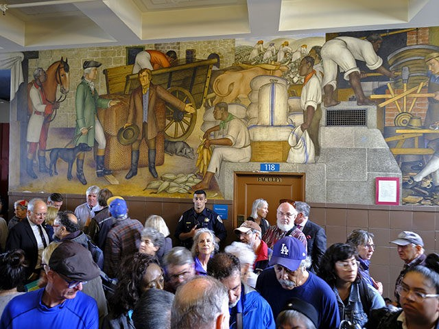 """People fill the main entryway of George Washington High School to view the controversial 13-panel, 1,600-square foot mural, the """"Life of Washington,"""" during an open house for the public Thursday, Aug. 1, 2019, in San Francisco. More than a 100 people packed the public high school to view a controversial …"""