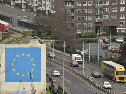A mural by British artist Banksy, depicting a workman chipping away at one of the stars on a European Union (EU) themed flag, is pictured in Dover, south east England on January 7, 2019. - Britain's battle over Brexit resumes Monday when parliament returns from its Christmas break to debate …
