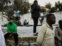 Men stand at an unofficial camp outside the refugee camp of Moria on the Greek island of Lesbos, on March 19, 2019. - When thousands of people fleeing war and poverty began arriving on their Greek island, many on Lesbos welcomed them. Four years later a sprawling local camp is …