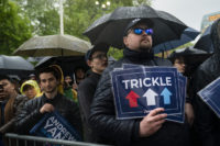 NEW YORK, NY - MAY 14: Supporters listen in the rain as Democratic presidential candidate Andrew Yang speaks during a rally in Washington Square Park, May 14, 2019 in New York City. One of Yang's major campaign promises is a universal basic income of $1,000 every month for every American …