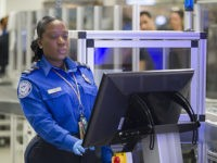 MIAMI, FLORIDA - MAY 21: Transportation Security Administration (TSA) agent, Roselie Pierre, keeps an eye on the 3-D scanner screen at the Miami International Airport on May 21, 2019 in Miami, Florida. TSA has begun using the new 3-D computed tomography (CT) scanner in a checkpoint lane to detect explosives …