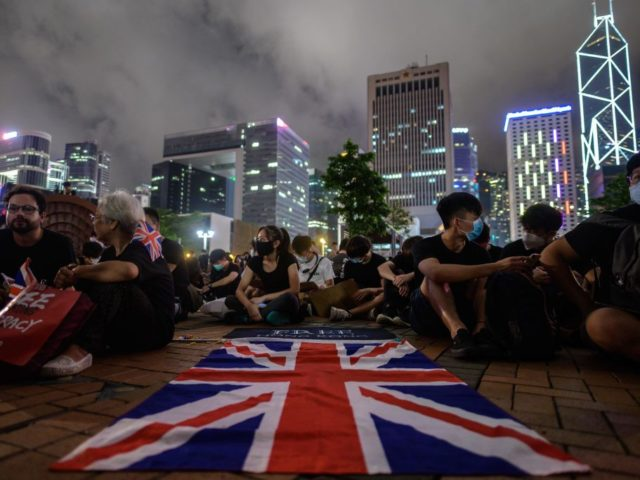 A British Union Jack flag is displayed as protesters gather along a fenced-off Victoria Harbour pier in Hong Kong, late on June 28, 2019, before midnight, when China's People's Liberation Army (PLA) will automatically be granted control of the pier under a 1994 British and Chinese agreement. - Hong Kong …