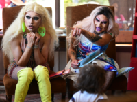 Drag queen Scalene Onixxx (R) gestures seated beside Athena Kills while reading during Drag Queen Story Hour at Cellar Door Books in Riverside, California on June 22, 2019. - Athena and Scalene, their long blonde hair flowing down to their sequined leotards and rainbow dresses, are reading to around 15 …