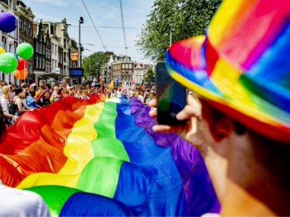 People take part in the Gay Pride Walk and hold a big LGBT flag during the opening of the Pride Amsterdam festival, in Amsterdam on July 27, 2019 (Photo by Robin UTRECHT / ANP / AFP) / Netherlands OUT (Photo credit should read ROBIN UTRECHT/AFP/Getty Images)