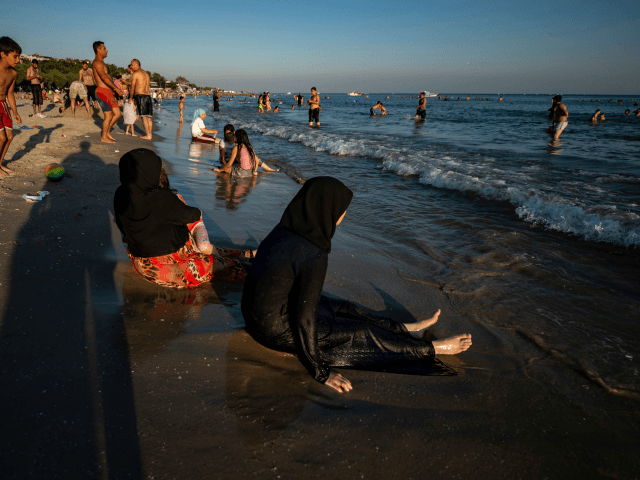 Syrian women sit on the beach at Menekse on July 28, 2019, in Istanbul. - Syrians living illegally in Istanbul have until August 20 to leave the city or face expulsion, authorities warned on July 22, as hostility mounts towards the millions of refugees in Turkey. Turkey has 3.5 million …