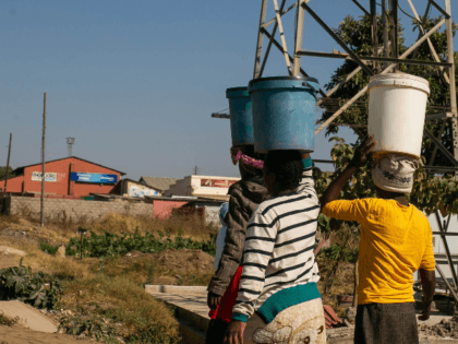 Women carry 20 litre containers of water in the streets of Mabvuku on August 1, 2019 in Harare, Zimbabwe. Zimbabwe is facing an acute water shortage after this year's drought, compounded by poor water management. Rainfall is down 25 percent from the annual average, according to the Zimbabwean government, leaving …
