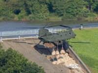 Personnel use a Royal Air Force (RAF) Chinook helicopter to lower bags of aggregate to reinforce the damaged spillway of the Toddbrook Reservoir dam above the town of Whaley Bridge in northern England on August 2, 2019. - Emergency services continued work to repair a damaged dam they fear could …