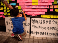 A boy writes on a Lennon Wall at a protest held by medics in the Central District of Hong Kong on August 2, 2019, in the latest opposition to a planned extradition law that was quickly evolved into a wider movement for democratic reforms. - Hong Kong civil servants on …