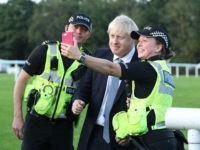 WHALEY BRIDGE, ENGLAND - AUGUST 02: Prime Minister Boris Johnson has a selfie with police officers as he arrives to meet emergency crews during a visit to Whaley Bridge Football Club as work continues at Toddbrook reservoir following a severe structural failure after heavy rain, on August 02, 2019 in …