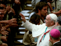 Pope Francis waves to faithful and wears a scout scarf given by a participant, during the Euromoot meeting (Federation of European Scouting) in the Paul VI hall at the Vatican, on August 3, 2019. (Photo by Filippo MONTEFORTE / AFP) (Photo credit should read FILIPPO MONTEFORTE/AFP/Getty Images)