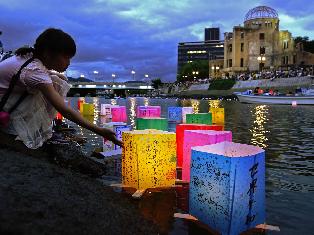 This August 6, 2019 picture shows a girl floating lanterns to mourn atomic bomb victims on the Motoyasu river beside the atomic bomb dome during the 74th anniversary of the atomic bombing in Hiroshima. - JAPAN OUT (Photo by JIJI PRESS / JIJI PRESS / AFP) / Japan OUT (Photo …