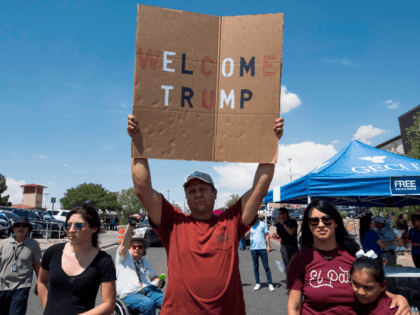 A Trump supporter holds a sign outside the makeshift memorial to the victims of the WalMart shooting that left a total of 22 people dead, in El Paso, Texas, on August 7, 2019. - President Donald Trump consoled victims of a mass shooting in Ohio on Wednesday but protesters and …