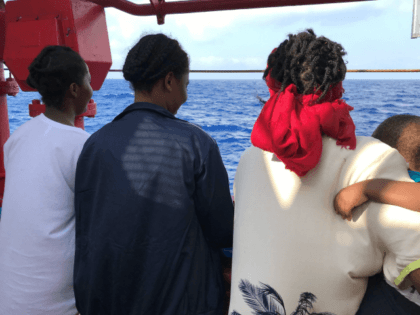 A woman named Bintu (R), holding her child, stands with two other migrant women aboard the Ocean Viking ship after being rescued from the Mediterranean Sea in the past 24 hours on August 10, 2019. - More than 80 migrants, mainly Sudanese men and adolescents, were picked up by the …