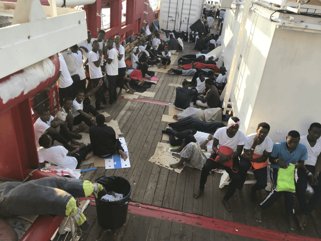 Rescued migrants rest on the desk of the 'Ocean Viking' rescue ship, operated by French NGOs SOS Mediterranee and Medecins sans Frontieres (MSF), during an operation in the Mediterranean Sea on August 12, 2019. - The rescue operation comes as a dispute escalates over which countries will take in migrants …