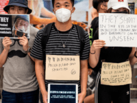 Protesters hold placards at Hong Kong's international airport following a protest against the police brutality and the controversial extradition bill on August 12, 2019. - Global stock markets dropped on August 12 as escalating protests in Hong Kong forced the closure of the financial hub's airport, adding geopolitical worries to …